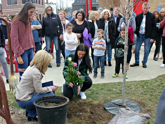 Roses are placed near the tree planted April 21, 2018