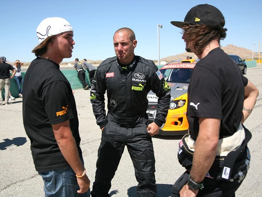Rickie Fowler, professional golfer, left; Dave Mirra, rally car driver and former BMX star; and Bucky Lasek, professional skateboarder, talk during the Subaru PUMA Global Rallycross Team Testing Day on June 27, 2012, in Rosamond, California.