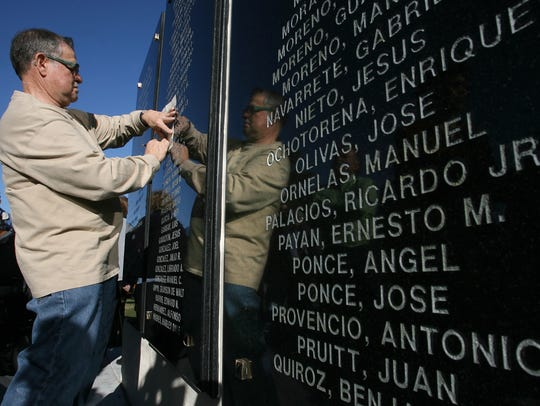 Eloiso de Avila Jr. takes a rubbing from the Men of Company E Memorial Wall, which bears his father's name: Elioso de Avila Sr. The wall was erected to honor the largely Hispanic 141st Infantry, 36th Division that fought in World War II.