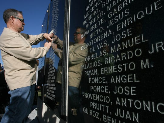 "Eloiso de Avila Jr. took a rubbing from the newly unveiled ""Men of Company E Memorial Wall"" which bears his father's name Elioso de Avila Sr.  The wall was erected to honor the largely hispanic 141st Infantry, 36th Division who fought in World War II."