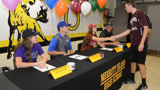 Alyssa Zwolensky, Brady McConnell, Kaley Verpaele and Connor Allen are congratulated by friends and family after signing college letters of intent Wednesday at Merritt Island High School.