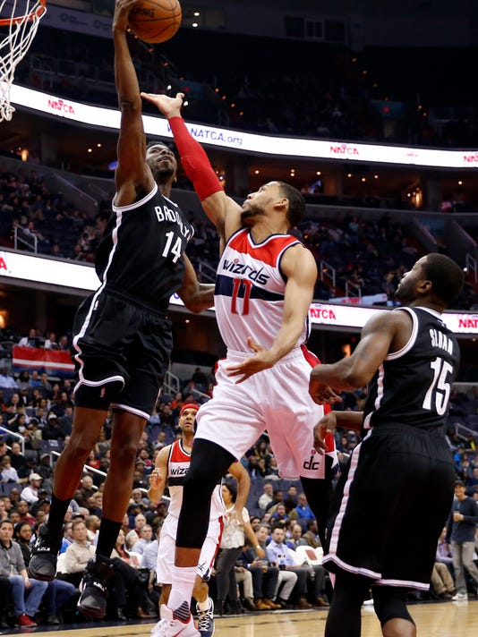 Brooklyn Nets center Henry Sims (14) blocks a shot by Washington Wizards guard Garrett Temple (17) with Brooklyn Nets guard Donald Sloan (15) at right, during the first half of an NBA basketball game Wednesday, April 6, 2016, in Washington. (AP Photo/Alex Brandon)