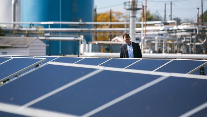Peter Ford, managing director at Freepoint Commodities, looks at the rows of solar panels in Newport as they gather at a press conference and signing held Wednesday afternoon announcing that New Castle County will create new rules to allow large scale solar farms in the county and a company wants to put one near Middletown.