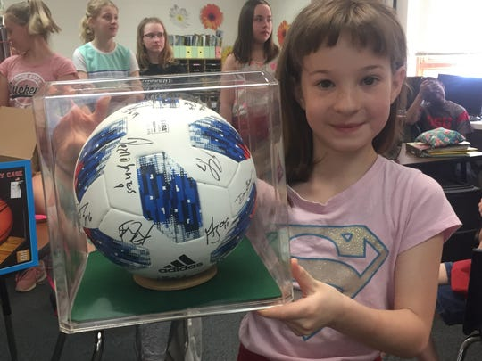 Among the items for auction is this autographed Crew ball, displayed by Jordyn Abel.