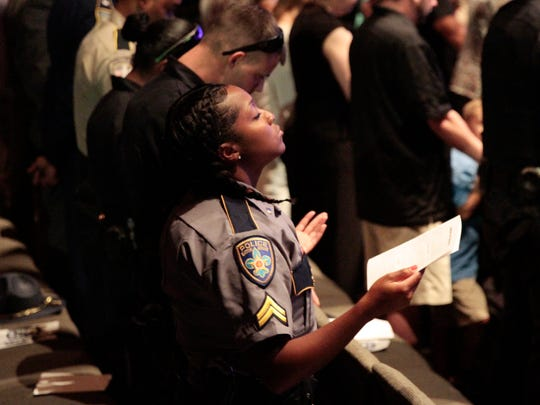 A Baton Rouge police officer prays during a memorial honoring three Baton Rouge law enforcement officers killed in a July 17 shootout, in Baton Rouge July 25.