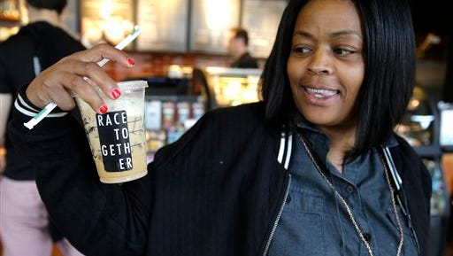 """Larenda Myres holds an iced coffee drink with a """"Race Together"""" sticker on it at a Starbucks store in Seattle, on Wednesday, March 18, 2015.  Baristas at stores in the U.S. were told to put the stickers on cups or write the words """"#RaceTogether"""" for customers in an effort to raise awareness and discussion of race relations."""