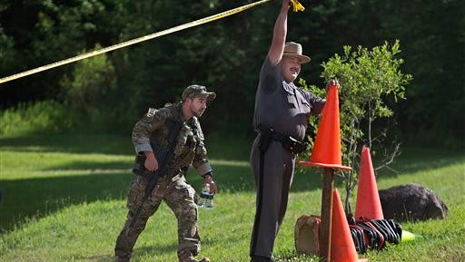 New York State Police Troop B Sergeant Chad Niles clears the way for an officer leaving the operations command post at Titus Mountain in Malone, N.Y.,  Friday, June 26, 2015.  One of two convicted murderers who staged a brazen escape from an upstate maximum-security prison three weeks ago was shot and killed by a border patrol agent in a wooded area 30 miles from the prison on Friday, and the other was on the run, authorities said.  (Jason Hunter/The Watertown Daily Times via AP)  SYRACUSE OUT
