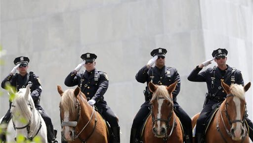Members of the Albany Police Department mounted division salute during a ceremony at the New York State Police Officers' Memorial on Tuesday, May 10, 2016, in Albany, N.Y. Law enforcement officials from across the state join together with elected officials each year to pay tribute to fallen officers.