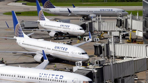 FILE - In this July 8, 2015, file photo, United Airlines planes are parked at their gates as another plane, top, taxis past them at George Bush Intercontinental Airport in Houston. United Airlines says it will raise the limit to $10,000 on payments to customers who give up seats on oversold flights and will increase training for employees as it deals with fallout from the video of a passenger being violently dragged from his seat.