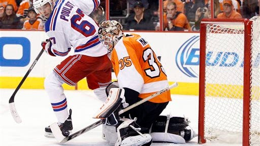Philadelphia Flyers' Steve Mason, right, stops the puck with his stick as New York Rangers' Benoit Pouliot, left, looks back for it during the second period in Game 4 of an NHL hockey first-round playoff series on Friday, April 25, 2014, in Philadelphia. (AP Photo/Chris Szagola)