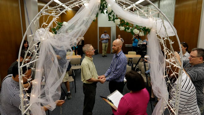 Bart Peterson, left, and Pete McNamara, center, are married by Marion County Clerk Beth White married in Indianapolis, Wednesday, June 25, 2014. A federal judge struck down Indiana's ban on same-sex marriage Wednesday in a ruling that immediately allowed gay couples to wed.