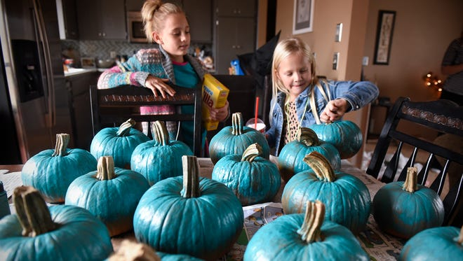 Pumpkins painted teal by Amber Wiese and her daughters Amara, left,  and Morgan fill the dining room table Monday, Oct. 30, at their home in St. Joseph. The teal pumpkins are a sign that allergen-free treats or toys are available at surrounding homes for Halloween.