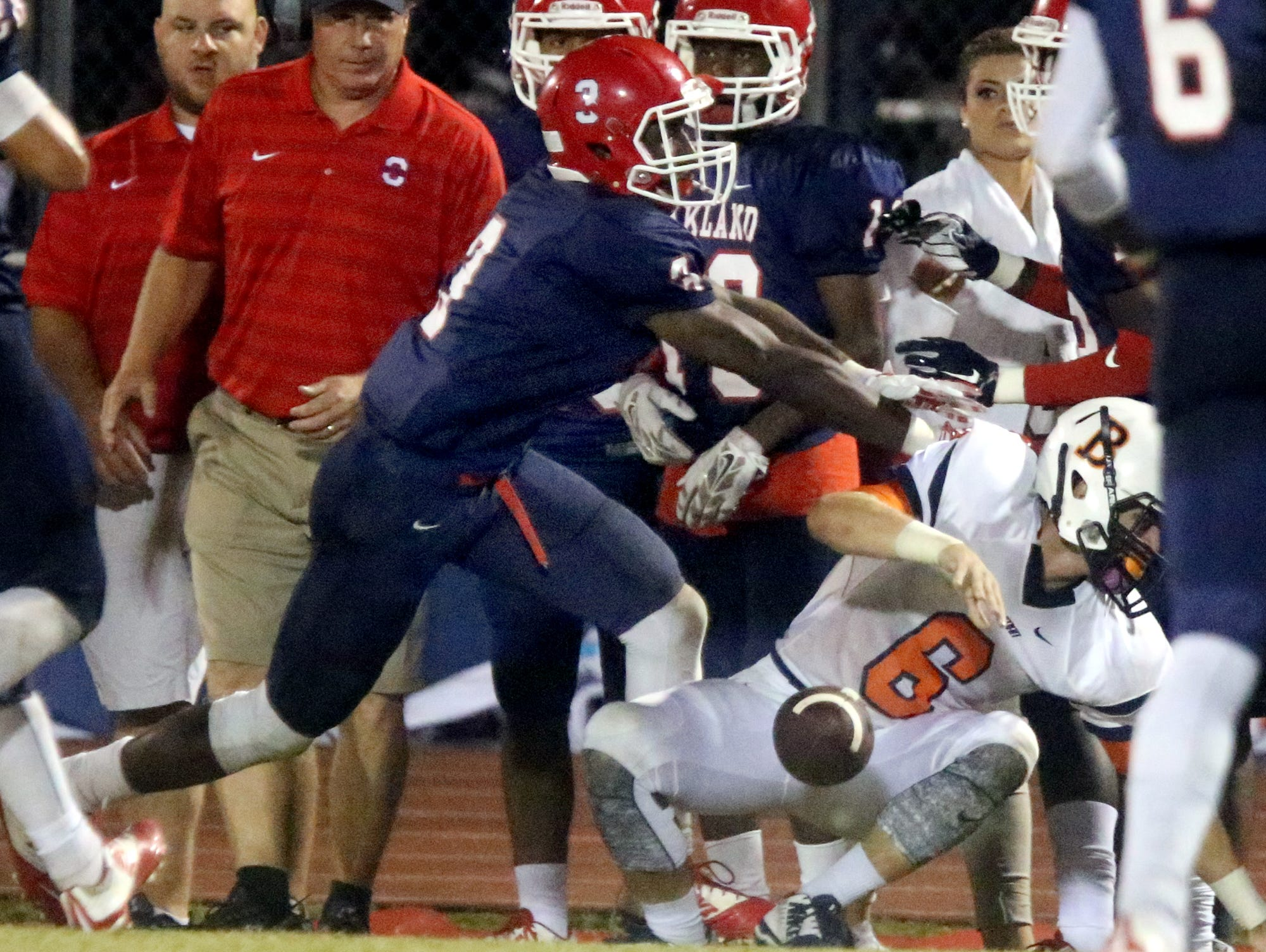 Blackman's Connor Mitchell (6) falls as hurts his knee after a catch and a run while Oakland's Wanya Moton comes in for the tackle, during the game at Oakland, on Friday Sept. 18, 2015.
