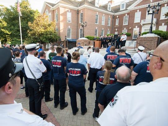 Volunteer firefighters listen as Warren Jones, executive