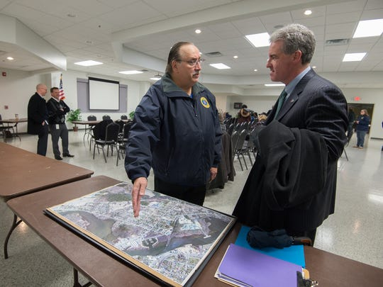 Blades Mayor David Ruff, left, talks with Shawn Garvin, secretary of the Delaware Department of Natural Resources and Environmental Control, next to a map of Blades. Recent tests have found PFC contamination in public drinking wells in Blades.