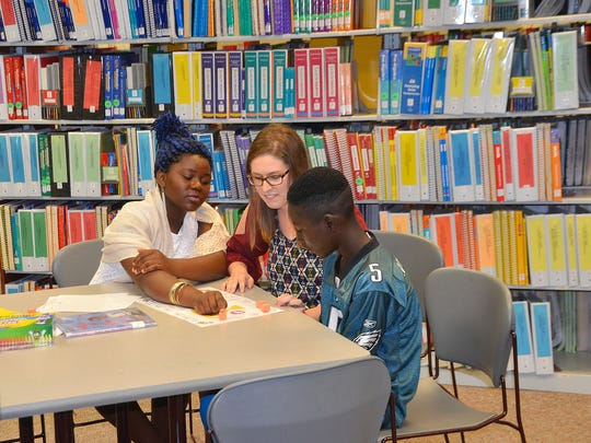 Katelyn Schmitt plays a word game with Risiki Barume,15, and Patrick Habimana, 13, refugees from the Congo. Evangel University offers a free Literacy Lab each summer for local students. Katelyn recently completed her Master of Education in Literacy at Evangel.