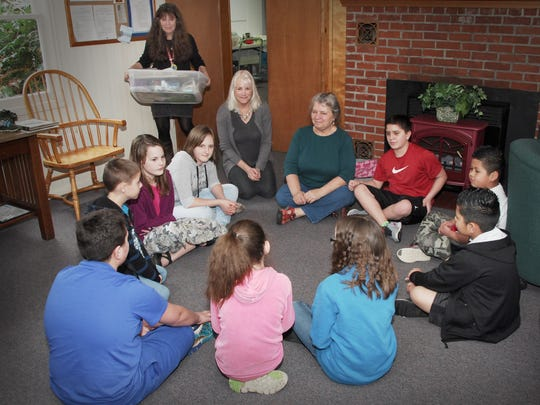 Instructors at the Ash Creek Arts Center Spring Summer Art Camp in the Parish Hall at St. Hilda's Episcopal Church in Monmouth meet with some of the children just prior to class time. Instructors include Sonia Allen, (standing), Kathy Lord, (center) and coordinator Francie Zandol, (right).