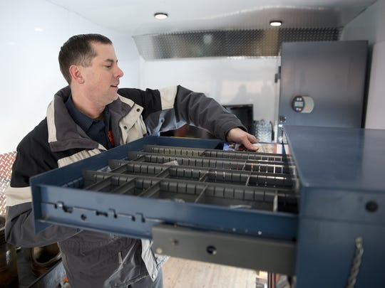 Mike Farrell, a diesel technology instructor at Fox Valley Technical College, grabs a set of brochures from the FVTC mobile diesel technology truck before talking with students at Kaukauna High School Wednesday, Jan. 27, 2016, in Kaukauna, Wis.  Danny Damiani/USA TODAY NETWORK-Wisconsin