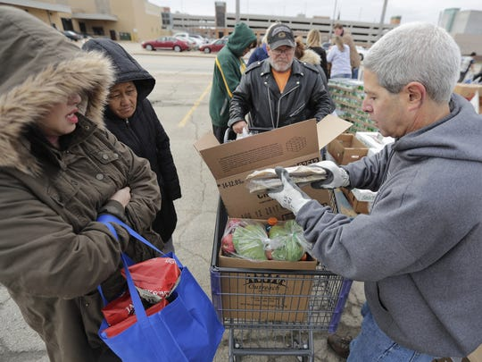 Robert Zizzo of The Green Bay Press-Gazette volunteers at the mobile food pantry event Friday in Appleton. It was the kickoff to the annual Stock the Shelves campaign.  Wm. Glasheen/USA TODAY NETWORK-Wisconsin
