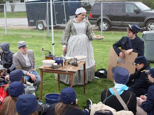 Alicia Shult, a Civil War re-enactor, cooked bacon