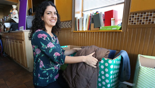 Sheila Angha, a personal chef with her business, Vibrant Baby Food, folds some donated clothing that she was collecting at a business on Ashford Avenue in Dobbs Ferry called Gourmet Home Chefs.