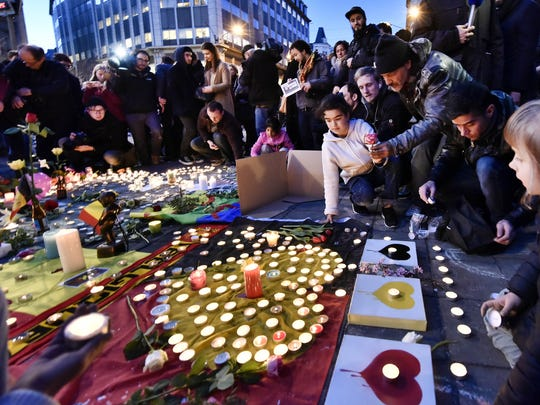 People bring flowers and candles to mourn for the victims