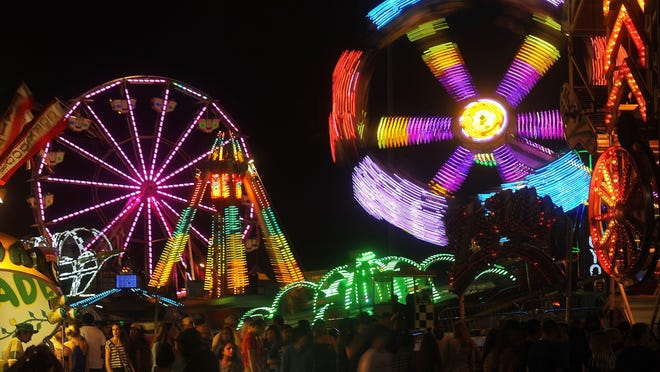Fairgoers mill about the midway at the W.H. Lyon Fairground during the Sioux Empire Fair on Aug. 6, 2015.