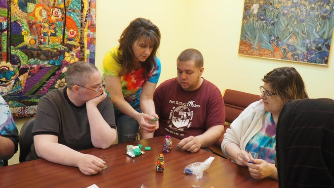 Trista Holz (center, in tie-dye shirt) shows Michael Alexander Wood (left), Brian Gebhart (in red) and Kimmer Brehmer (right) how to decorate their wish glasses Wednesday. Holz does art projects with NAMI members every week to showcase how to deal with mental illness symptoms in a healthy, safe way.