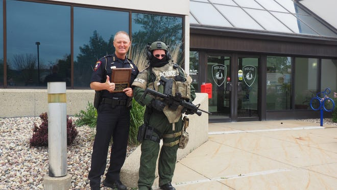 Fond du Lac Fire/Rescue Chief Peter O'Leary (right) poses with Fond du Lac Police Department Chief Bill Lamb at the police department Thursday. O'Leary dressed in police SWAT gear as a result of losing a challenge against the police department to raise the most money for the St. Baldrick's Foundation.