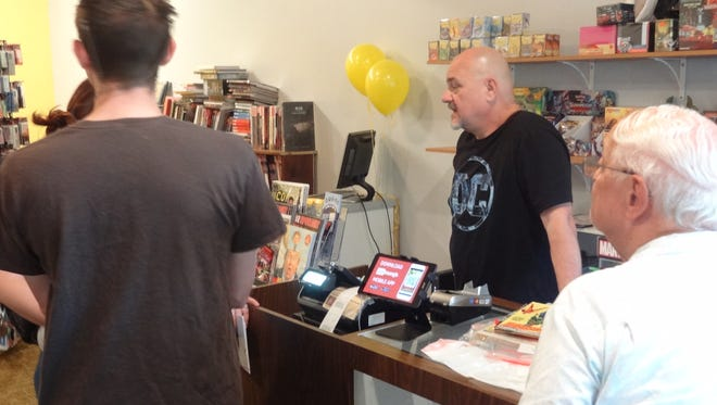 Rick Schreiber, center, talks to customers at his new location in Downtown Titusville.