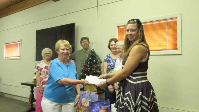 West Side United Methodist Church Mission chairman Alta Buford-Cox presents a check and gifts to Tina Mann of the Great Falls Children's Receiving Home. Pastor David Odell and members of missions committee were present.