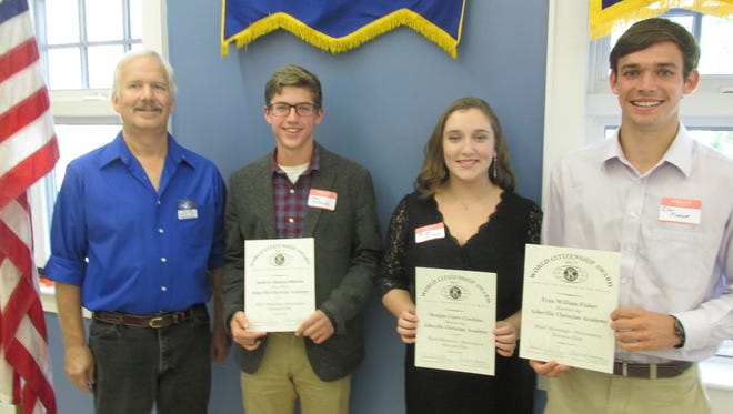 From left, Kiwanis Club president Dave Wilks poses with essay winners Drew Sikkink, Morgan Ciochina and Evan Fisher.