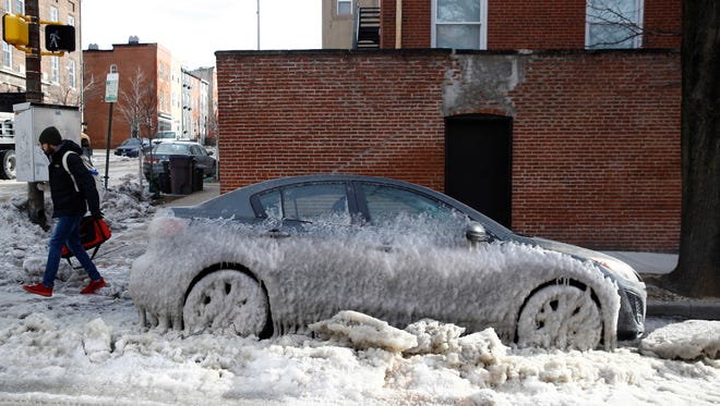 A car is partially covered by ice following an overnight water main break in Baltimore on Jan. 3, 2018.