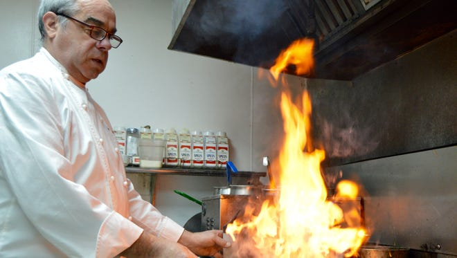 Jim Hughes, executive chef and owner of Restaurant 213 in Fruitland, sets a dish a-blaze.