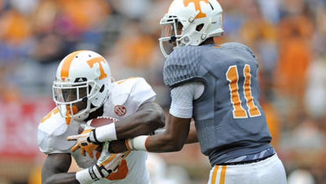 Quarterback Josh Dobbs, right, hands off to running back Alvin Kamara during Tennessee's Orange and White Game in April.