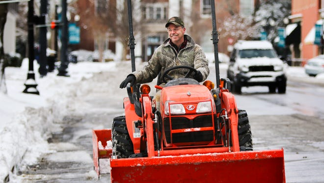 East Main Church of Christ Elder Brad Rowley clears the parking spaces in front of the East Main building and First Baptist Church Saturday morning.