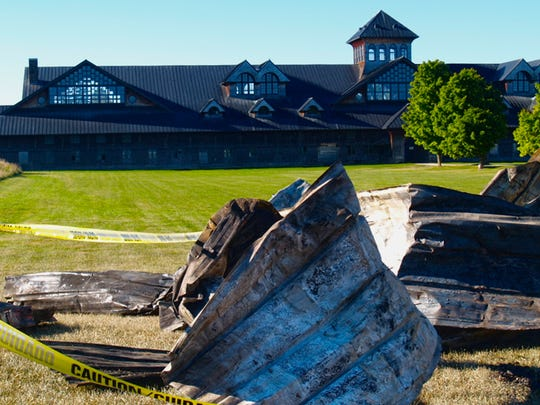 The Breeding Barn overlooks the ashes, bits of charred wood and twisted metal that remain of the Old Dairy Barn at Shelburne Farms on Monday, Sept. 12, 2016. The historic structure caught fire early Sunday morning.