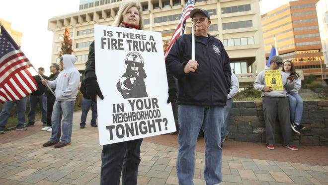 Susan Wiley and Wilmington Fire Department Capt. Kevin Turner stand with other fire department members and supporters as they gather opposite the Louis L. Redding City County Building in late November to protest the city's decision to resume a payroll savings plan by reducing the number of on-duty firefighters.