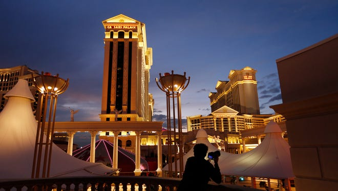 A man takes pictures of Caesars Palace hotel and casino, in Las Vegas.