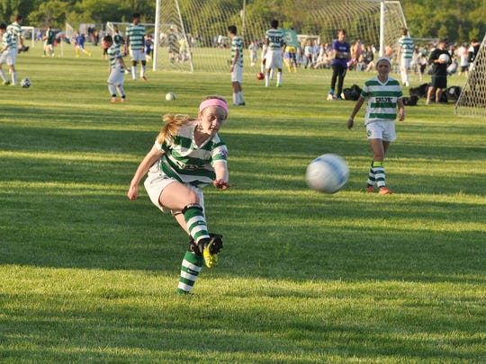 Kicking the ball to a teammate is Brenna Heins of Canton