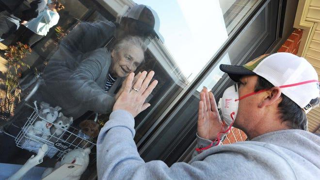 Kevin Joyce visits his mother Patricia Joyce of Brockton, who beat the coronavirus at Saint Joseph Manor Health Center Wednesday, May 13, 2020. [Marc Vasconcellos/The Enterprise]
