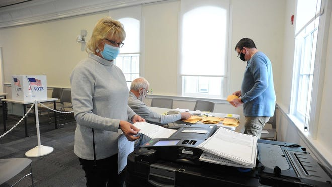 Poll worker Joanne May processing mail-in ballots at the Academy Building in Bridgewater, Wednesday, Oct. 28, 2020.