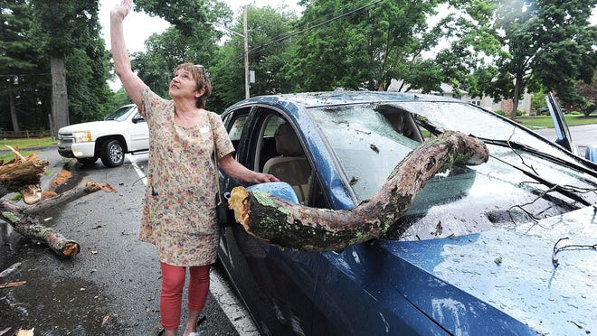 Driver Debby Clish, of East Bridgewater, points to the sky to 'thank God' after a tree snapped on Pearl Street, with a thick branch impaling the windshield of a car driving in the area of Tiffany Drive in Brockton, Wednesday, July 1, 2020.