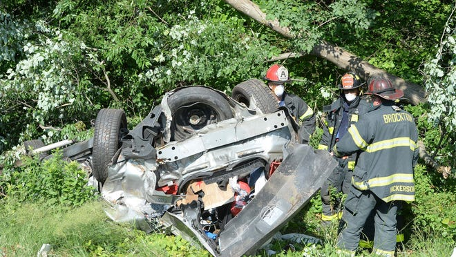 A mangled vehicle rests on its roof in the grassy area to the right of Route 24 south, just before exit 17B for Route 123, after a single-vehicle crash, Sunday, June 21, 2020.