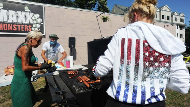 From left, Donna Carbone, Michael Varner and Susan Williams get cooking during a community assembly/barbecue in Stoughton, on Saturday, July 4, 2020.