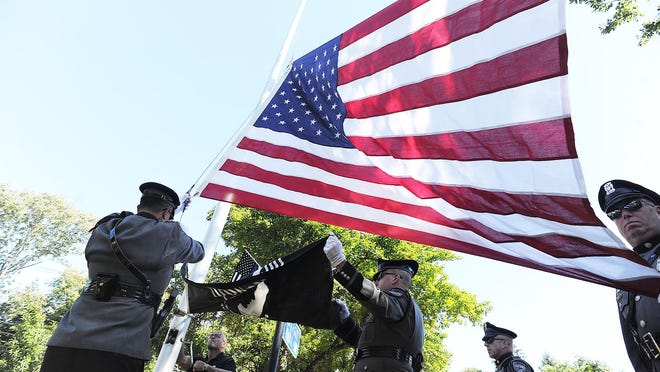 Volunteer Michael Varner, with the help of the Stoughton police honor guard, raise the American and POW/MIA flags. A flag raising dedication ceremony was held the at Peter J. McGarvey Memorial Park in Stoughton, Saturday, Sept. 19, 2020. The park has been there for years, but it never had a flagpole. Many citizens and businesses chipped in to make the flagpole possible.