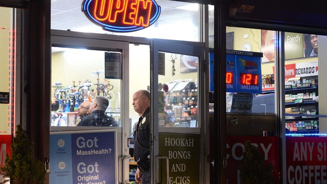 FILE - In this April 1, 2020, photo, police investigate after an armed robbery at Sam's Food Store, at 390 Pleasant St. in Brockton. The store was robbed again Sunday, Oct. 4, 2020.