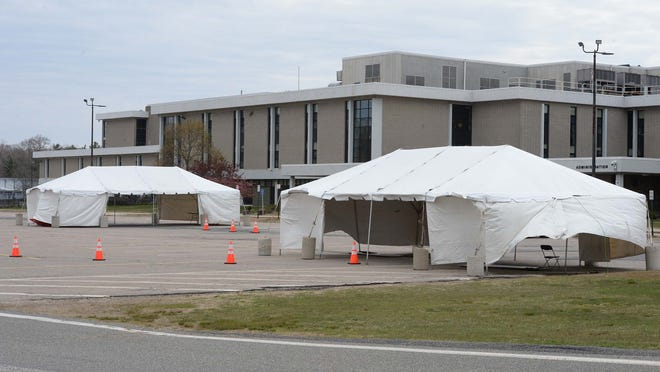 FILE - Tents set up for coronavirus testing are seen on the Brockton High School campus, Thursday, April 30, 2020.