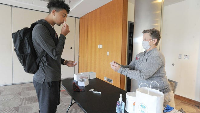 Student Damani Domerson, 18, of Boston, takes a self-administered COVID-19 test, directed by Director of Social Medicine Jeanne O'Brien, on the campus of Bridgewater State University, Wednesday, Oct. 21, 2020.