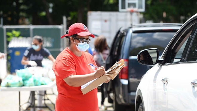 FILE - In this July 10, 2020, photo, volunteer Delmy Lopez takes information from a person inside a vehicle as the Brockton Workers Alliance Food Distribution Program gives out food at the Warren Avenue Baptist Church, also known as Iglesia Baptista Church, in Brockton.